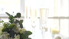 Two crystal glasses of champagne and a wedding bouquet. On the table closeup stock video