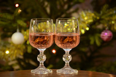 Two crystal glasses of pink wine on the background Christmas tree. Glasses of wine on the table nea the Christmas tree Stock Image