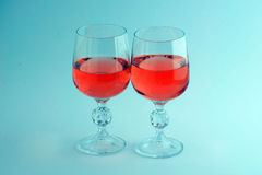 Two crystal glasses of pink wine isolated. Glasses of wine on the blue background Stock Image