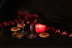 Two crystal glasses of wine, candles and sweets. Red is the color of passion. Romantic date. Be my Valentine stock photography