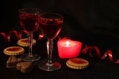 Two crystal glasses of wine, candles and sweets. Red is the color of passion. Romantic date. Be my Valentine stock photos