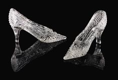 Crystal shoes on a black mirror. Two crystal shoes of the Cinderella stand on a black mirror Stock Photography