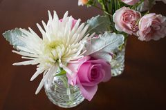 Two crystal vases with flowers on dark wood table Royalty Free Stock Image