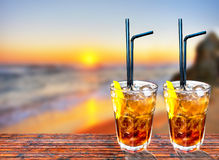 Two Cuba libre exotic tasty cocktail with beautiful sunset backg Royalty Free Stock Image