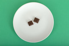 Two cubes of Chocolate on a plate. 100 calorie portion of plain chocolate on a plate against a green background Royalty Free Stock Image
