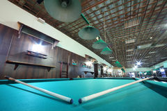Two cues are on billiard table. With green cloth inside club with metal lamps stock images