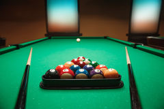 Two cues and pyramid on a billiard table. Royalty Free Stock Photography
