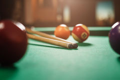 Two cues and spheres on a billiard table. Stock Photography