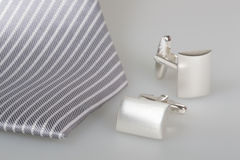 Two cufflinks and silk tie Royalty Free Stock Images