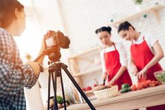 Two culinary bloggers dicing peppers with knives to camera. Two culinary bloggers in red aprons dicing peppers with knives to camera stock photos