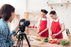 Two culinary bloggers dicing peppers with knives to camera. Two culinary bloggers in red aprons dicing peppers with knives to camera stock photography