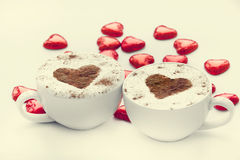 Two cup of coffee with heart symbol and candy around. Royalty Free Stock Photos