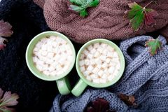 Two cup of coffee or hot chocolate with marshmallow near three knitted grey, black and brown sweater or  knitted blanket. Autumn c Royalty Free Stock Image