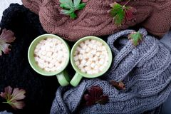 Two cup of coffee or hot chocolate with marshmallow near three knitted grey, black and brown sweater or  knitted blanket. Autumn c Stock Photography