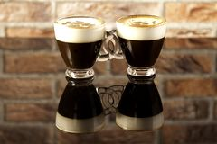Two cup of coffee linked. With reflection on brick background stock photo
