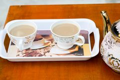 Two cup of coffee on a tray on red table. Two cup of coffee on a red table. this coffee is made by milk Royalty Free Stock Images
