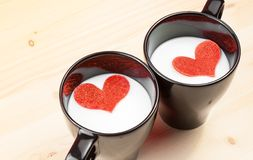 Two cup of milk with decorative hearts on wood table, concept of valentine day Royalty Free Stock Photography