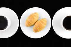 Two cup og coffe and croissant in black. Background Royalty Free Stock Photography