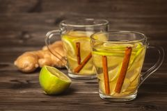 Two cup of soothing tea with ginger, lime and cinnamon on wooden. Background, close up Stock Image