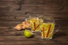 Two cup of soothing tea with ginger, lime and cinnamon on wooden. Background, healthy lifestyle concept,  copy space Stock Photo