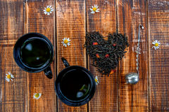 Two cup of tea near dry leaves  black  make in heart on wooden background  Vintage strainer.  concept.  . Top view. Closeup. Love. Royalty Free Stock Photos