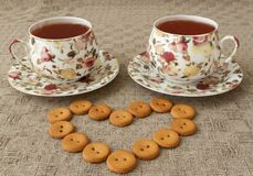 Two cup of tea and some cookies on table. Cup of tea and some cookies in heart form on linen tablecloth Royalty Free Stock Photos