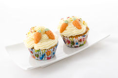 Two cupcake. Buttercream on a plate and sprinkles and carrot royalty free stock photography
