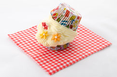 Two cupcake buttercream. On a red patterned napkin and flower royalty free stock image