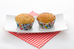 Two cupcake on a napkin. Two cupcake on a red patterned napkin and plate royalty free stock photo