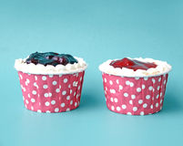 Two cupcake ornaments on blue background Royalty Free Stock Photography