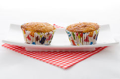 Two cupcake on a plate. Two cupcake on a red patterned napkin and plate Royalty Free Stock Photo