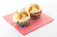 Two cupcake on a red patterned napkin. Two cupcake buttercream on a red patterned napkin and sprinkles and carrot royalty free stock images
