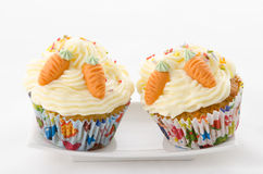 Two cupcake sprinkles and carrot. Two cupcake buttercream on a  plate and sprinkles and carrot Stock Photography