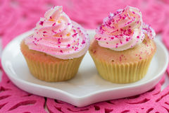 Two cupcake on white heart shaped plate, on pink background Royalty Free Stock Photos