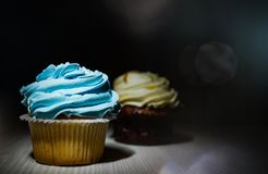 Two cupcakes with buttercream on wooden table against dark background Royalty Free Stock Photography