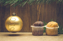 Two cupcakes and Christmas tree decoration. Christmas toy and two cupcakes Royalty Free Stock Photography