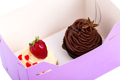 Two Cupcakes are in the Delivery Box over white background.  Royalty Free Stock Photos