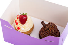 Two Cupcakes are in the Delivery Box over white background.  Stock Photo