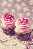 Two cupcakes with rose flowers Royalty Free Stock Photos