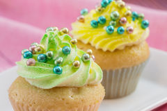Two cupcakes  with yellow and green  buttercream Royalty Free Stock Images
