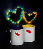 Two cups on a black background with bokeh Royalty Free Stock Photos