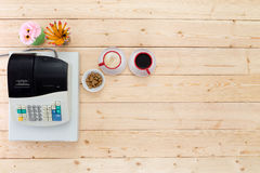 Two cups of black coffee alongside a till. Or cash register in a business on a plain wooden table or counter, viewed from above with copy space Royalty Free Stock Photo