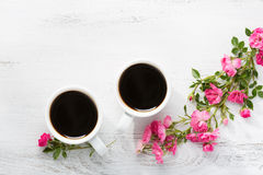 Two cups of black coffee and branch of small pink roses. Royalty Free Stock Photo