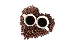 Two cups of black coffee and a heart made of coffee beans on white backgroung isolated top view. Two cups of black coffee and heart made of coffee beans on white royalty free stock photo