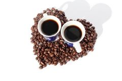 Two cups of black coffee and a heart made of coffee beans on white backgroung isolated top view stock photos