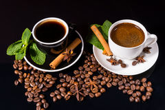 Two Cups of Black Coffee with Roasted Beans. High Angle Still Life of Two Cups of Black Coffee Garnished with Fresh Mint, Cinnamon Sticks and Star Anise on Black Royalty Free Stock Photography