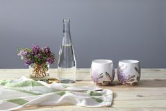 Two cups, bowl with water, towel, spring flowers on the wooden desk. Sunny morning. Breakfast. stock images