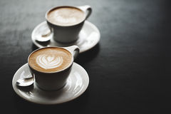 Two cups of cappuccino on black table Royalty Free Stock Photo