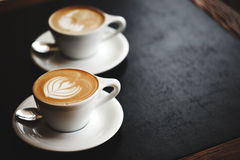 Two cups of cappuccino on black table Royalty Free Stock Image
