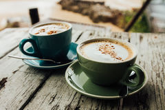 Two cups cappuccino coffee stand on wooden table. Green and blue cup coffee Royalty Free Stock Images